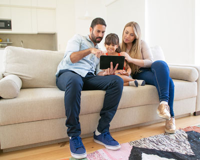 Cute young family couple with little girl sitting on couch in living room using computer technology tablet - Best Visa and Immigration Consultants in India